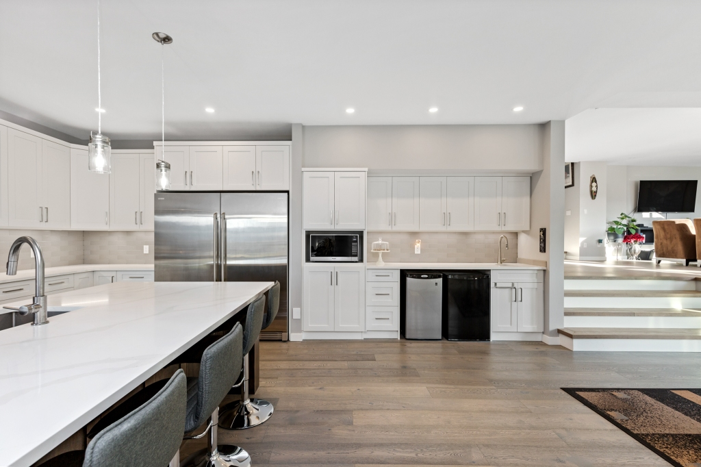 """Beautiful """"sunken"""" kitchen area - I love the mix of wood with the cabinetry I am seeing more and more of these days.  #canadianhomebuilders #kamloopsphotographer #lorriejanephotography #7pointmillworks #design #carpentry #woodworking #millwork #wood #finish #carpentry #customcabinets #customwoodwork #architecturalmillwork #architecturalwoodwork #chbabc #georgieawards #canadianhomebuildersassociation #kamloopsbc #luxury #chbahousingawards #kamloopsbuilder #interiorsphotography #interiordesign #interiordesigner #architecture #supportlocal #smallbusiness #kamloopsnow #kamloopsmatters"""